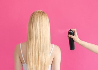 Hairstyle Concept photo in back view Woman's hand is spraying fixative spray on strands of a...