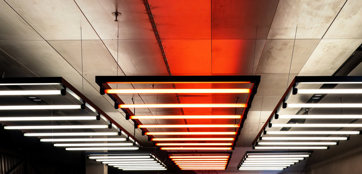 Ceiling with hanging down neon tubes. Lighting for halls, offices and large buildings
