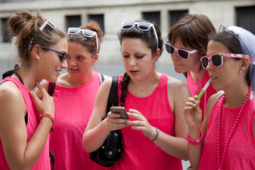 Group of young girls in pink T shirts looking their way on the telephone