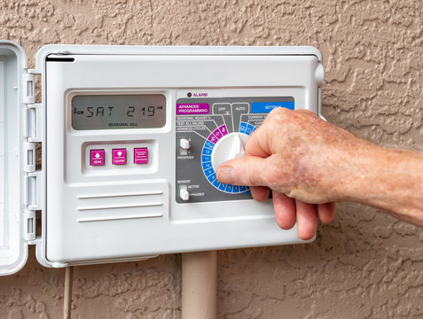 Automatic electric outdoor irrigation timer. Closeup of male hand setting programmable lawn watering system.