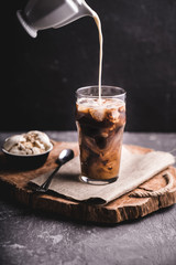 Iced coffee with milk. Preparation of iced coffee. Shot with streaks of milk in black coffee on dark concrete background and wooden tray.