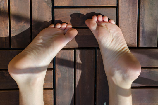 Child feet close-up on the wooden floor on the balcony on sunny day. Child lying on the wooden floor.