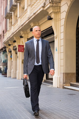 Full-length portrait of businessman walking on street
