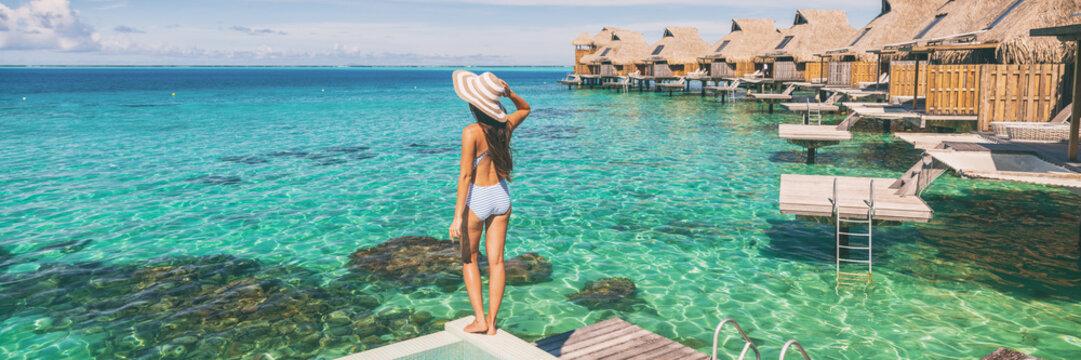 Travel luxury resort panoramic banner woman tourist enjoying view from overwater bungalow hotel in Maldives panorama. Paradise honeymoon destination.