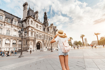 Attractive girl traveler with a cute backpack enjoys the view of the stunning Gothic architecture of the old town Hall in Paris. Your holidays and adventures in Paris Wall mural