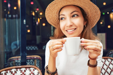 Portrait of young Asian woman drinking coffee in a cafe. Focus on white cup