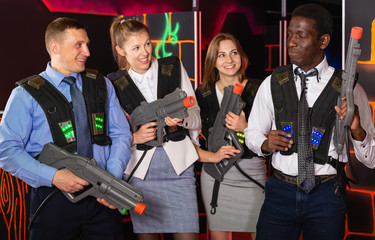 Group of glad co-workers holding laser guns