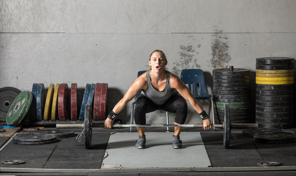 Young woman lifting heavy weights in grungy gym.