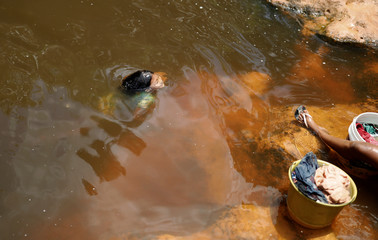 An Arara indigenous girl bathes in a river while her mother washes clothes at the village of Arado
