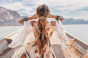 fashionable young model in boho style dress on boat at the lake Wall mural