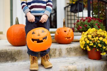 Little boy at halloween celebrations party. Child holds a bucket shaped like a halloween pumpkin jack o lantern.