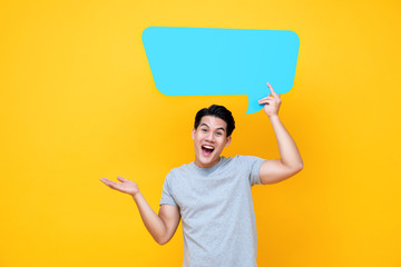 Excited young handsome Asian man with speech bubble