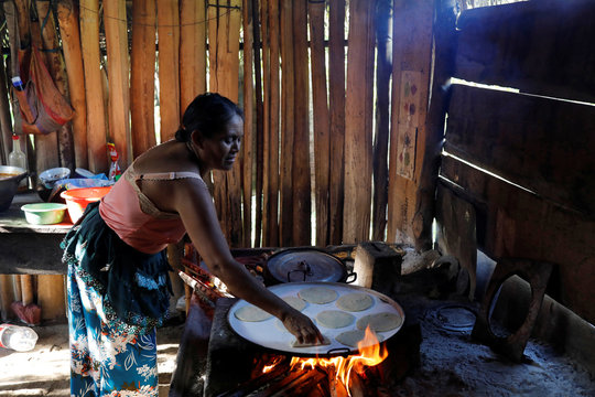 A woman prepares tortillas at her home during a temporary state of siege, approved by the Guatemalan Congress following the death of several soldiers last week, in the community of Semuy II, Izabal province