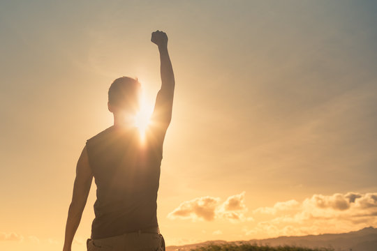Strong man with fist up into the sky. Competition, determination and finding strength concept.