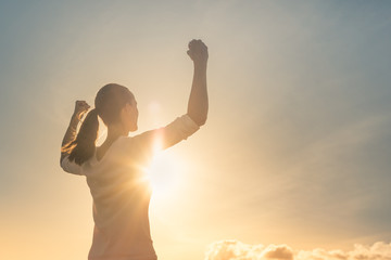 Strong confident woman flexing arms facing the sunset.