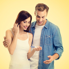 Square composition picture of young amorous happy couple, finding out results of a pregnancy test, on yellow background