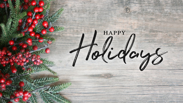 Happy Holidays Text with Holiday Evergreen Branches and Berries Over Rustic Wooden Background