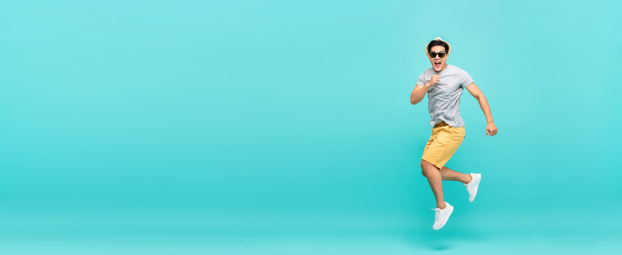 Amazed handsome Asian tourist man in summer outfit jumping