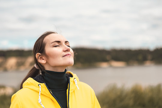 Portrait of a young woman in nature in a yellow jacket breathing fresh clean cool autumn air with a copy space