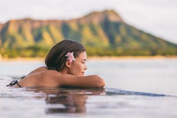 Wall Mural - Luxury resort wellness pampering spa lifestyle Asian woman relaxing in infinity swimming pool of outdoor hotel on Waikiki beach, Honolulu, Hawaii travel.