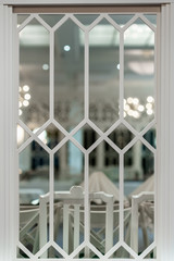 Beautiful white decorative vintage indoor dining room window with table setting in the background.