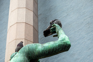 Closeup of two city pigeons sitting on a green bronze statue arm. One bird sleeping.