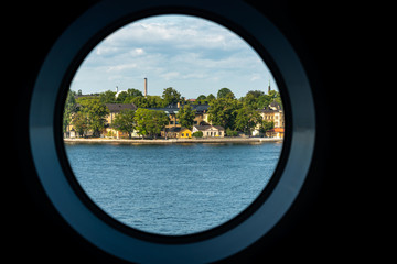 City summer landscape view of Stockholm seen from inside a ship cabin with round peep-hole window.