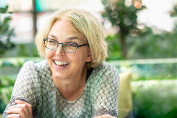 Closeup outdoor nature portrait of blond happy smiling mature woman in her fifties wearing glasses.
