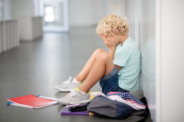 Blonde curly boy sitting on the floor and crying after bullying