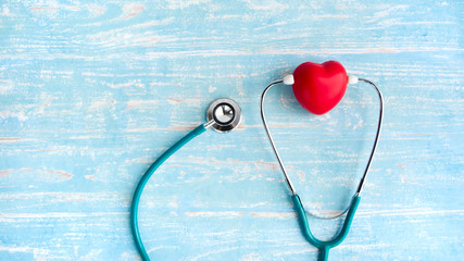 Red heart with stethoscope on pastel blue wooden background with copy space. Heart health care, hospital, insurance and world health day concept.