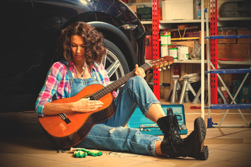 beautiful brunette car mechanic with a guitar sitting in a garage
