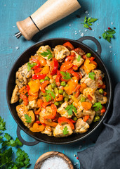 Chicken Stir fry with vegetables on blue table.