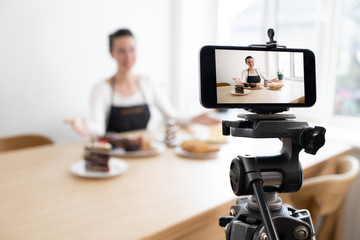 Woman vlogger recording video for food channel. Cooker shef recording a video for vlog with a phone