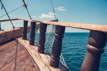The bow of an ancient ship. Vintage ship at sea. View of the sea through the beams and the side of an old wooden ship, rapidly sailing on the sea