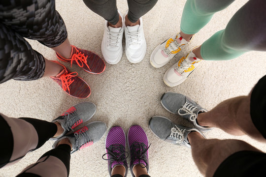 Closeup of athletes wearing sports shoes and standing in circle on beige carpet, top view. Space for text