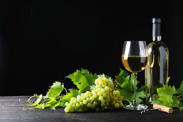 Fresh ripe juicy grapes with wineglass on grey table against black background, space for text