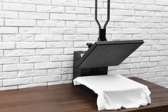Heat press machine with t-shirt on wooden table near white brick wall. Space for text