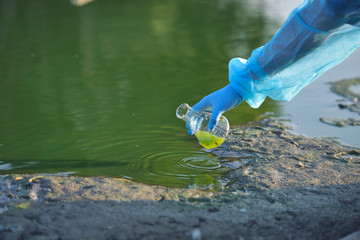 Close-up environmentalist hand of a researcher in a process of taking a sample of contaminated water from a lake