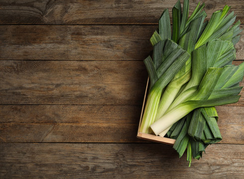 Crate of fresh raw leeks on wooden table, top view with space for text. Ripe onion