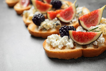 Bruschettas with cheese, figs and blackberries on grey table, closeup