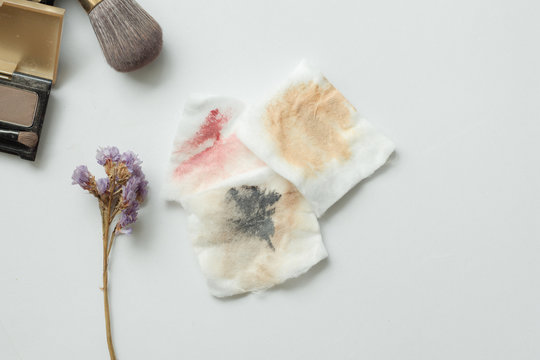 Top view of dirty cotton pads with make up on white background. accessories to make up removing.