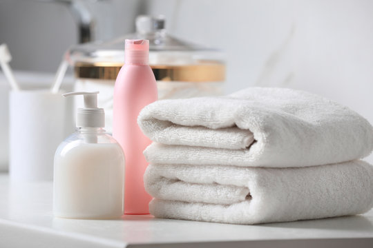 Folded towels and toiletries on white table in bathroom