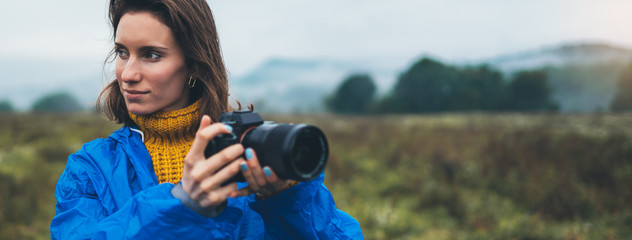photographer tourist girl in blue raincoat hold in female hands photo camera take photography foggy mountain, traveler shooting autumn nature, click on camera technology, hobby concept free space