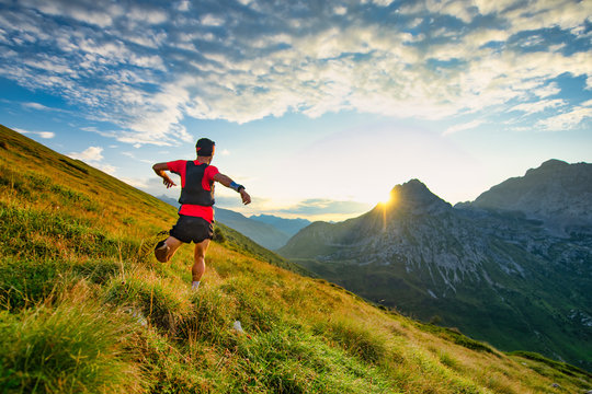 Runner skyrunner on a mountain meadow at dawn