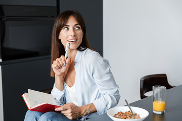Cheery woman indoors at home at the kitchen have a breakfast eat corn flakes while writing notes in notebook.