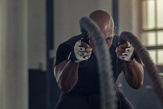 Black man doing intensive battle rope workout