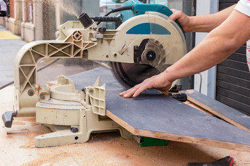 Male carpenter hands cutting laminated wood panels with a circular saw in the street.