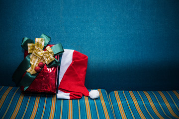 Merry Christmas background concept. Red gift box and Santa hat on blue sofa with free space for text.