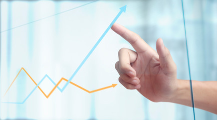 Hand touching a graphs of financial indicator chart