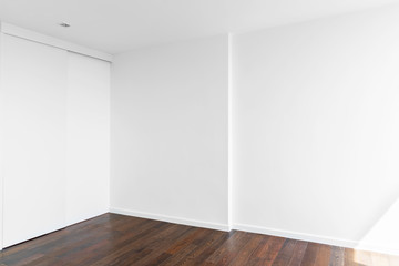 Empty white wall in room with wooden floor. Abstract and architecture background.